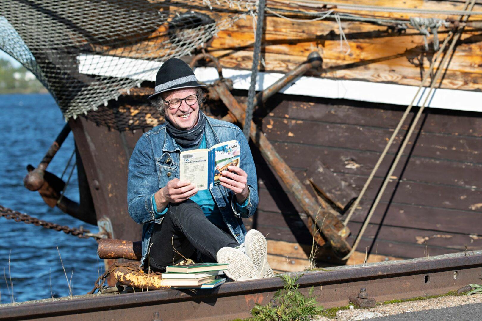 Toimittaja Ville Vanhala huomasi, että Pertsan ja Kilun seikkailuihin saa autenttista tunnelmaa, kun niitä lukee Kotkan satamassa. Kirja innosti vieläkin. © Pekka Nieminen