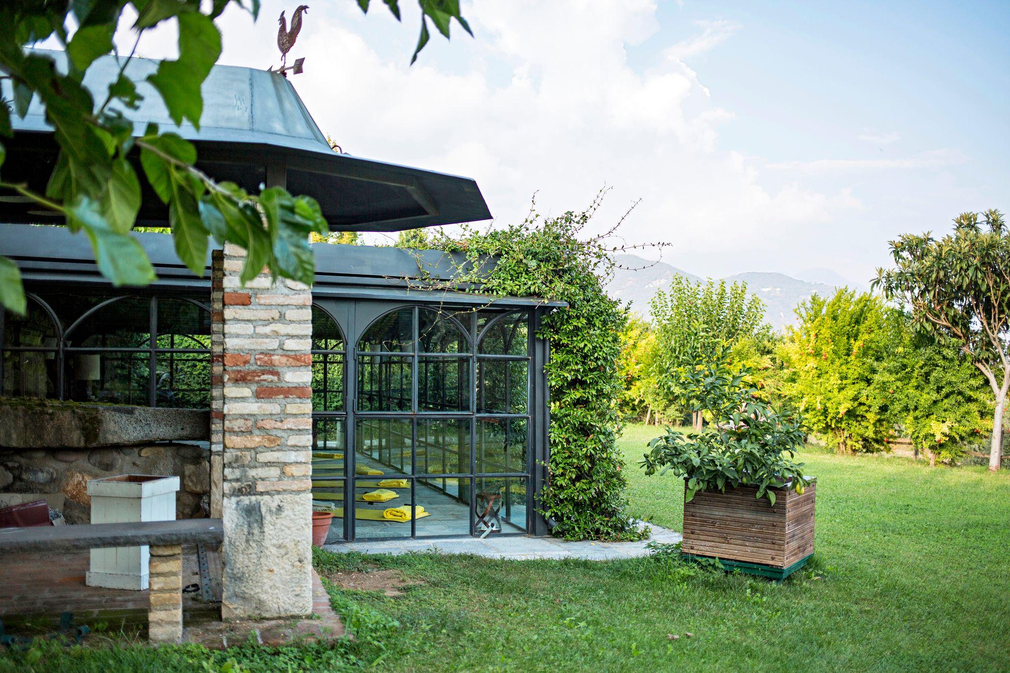 Puutarhan pergolan avattavat lasiseinät luovat turvallisen paikan joogatunneille.