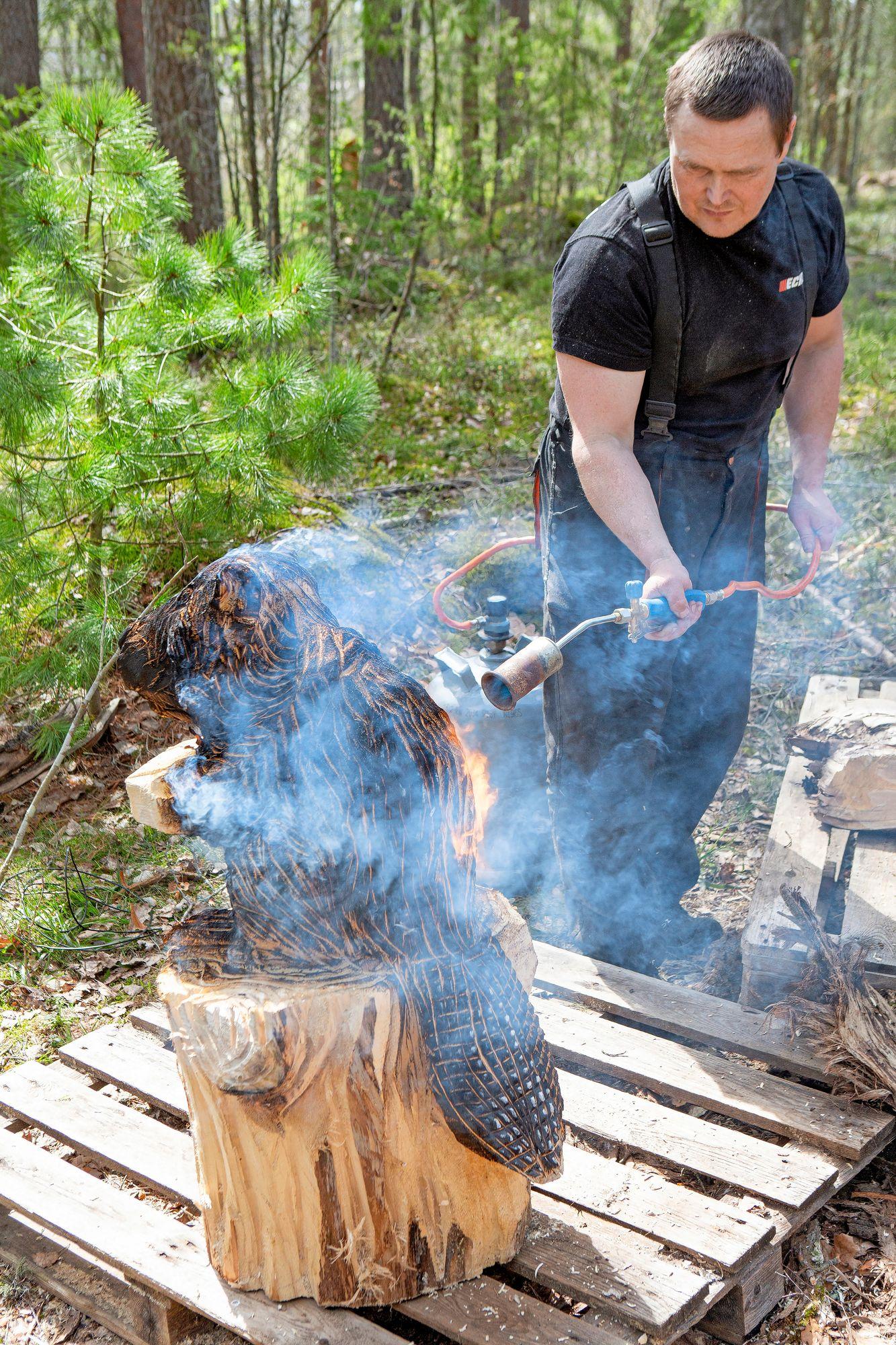 August polttaa puun pinnan tummaksi kaasupolttimella. Kauniin ulkonäön lisäksi se myös suojaa puun pintaa. © Tiiu Kaitalo