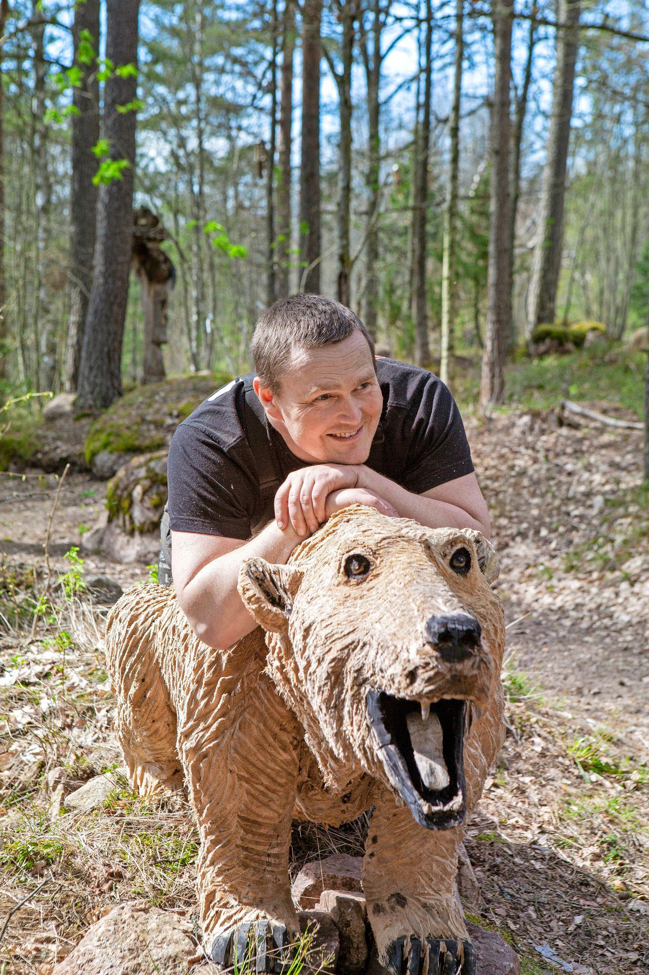 Puusta voi tehdä mitä vain, toteaa August Eskelinen veistämänsä karhun selässä. © Copyright Tiiu Kaitalo