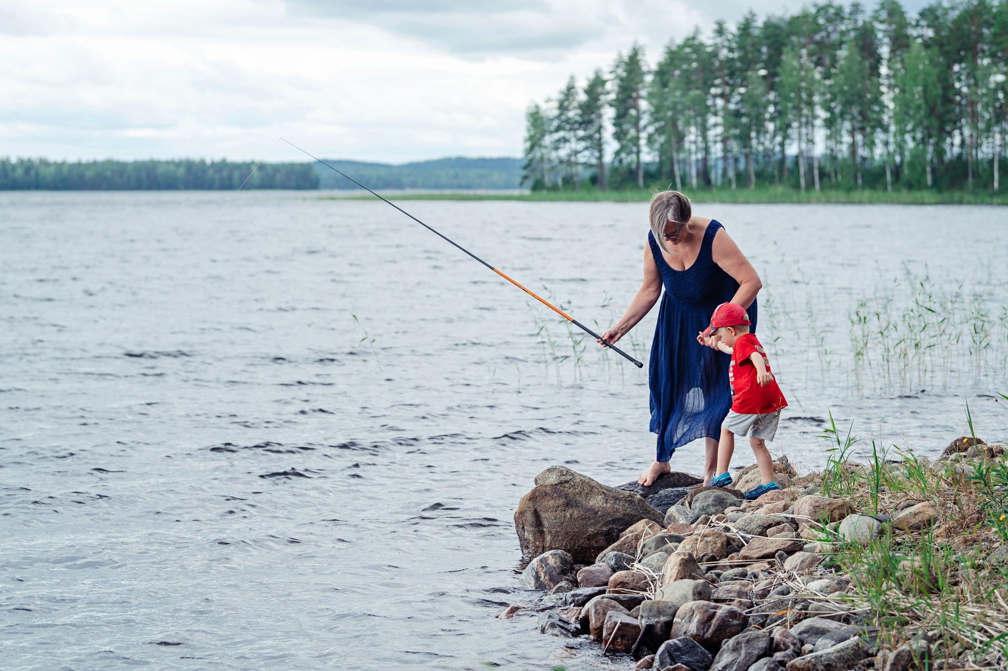 Mummi laittaa madon koukkuun. Innokas kalastaja Jimi toivoo ahvenia. © Pihla Liukkonen