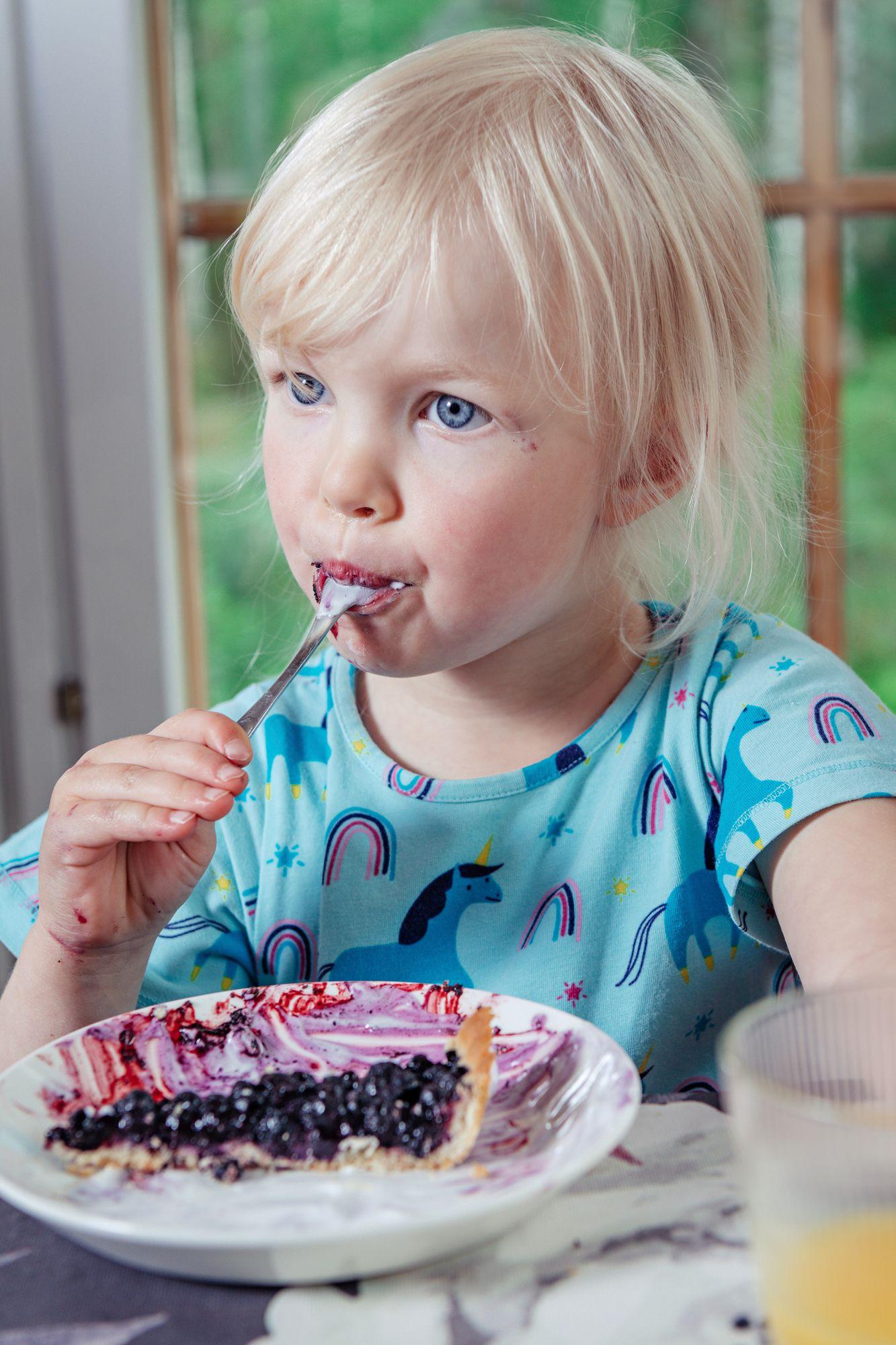 Itse poimituista mustikoista leivottu piirakka maistuu Alinalle. © Pihla Liukkonen