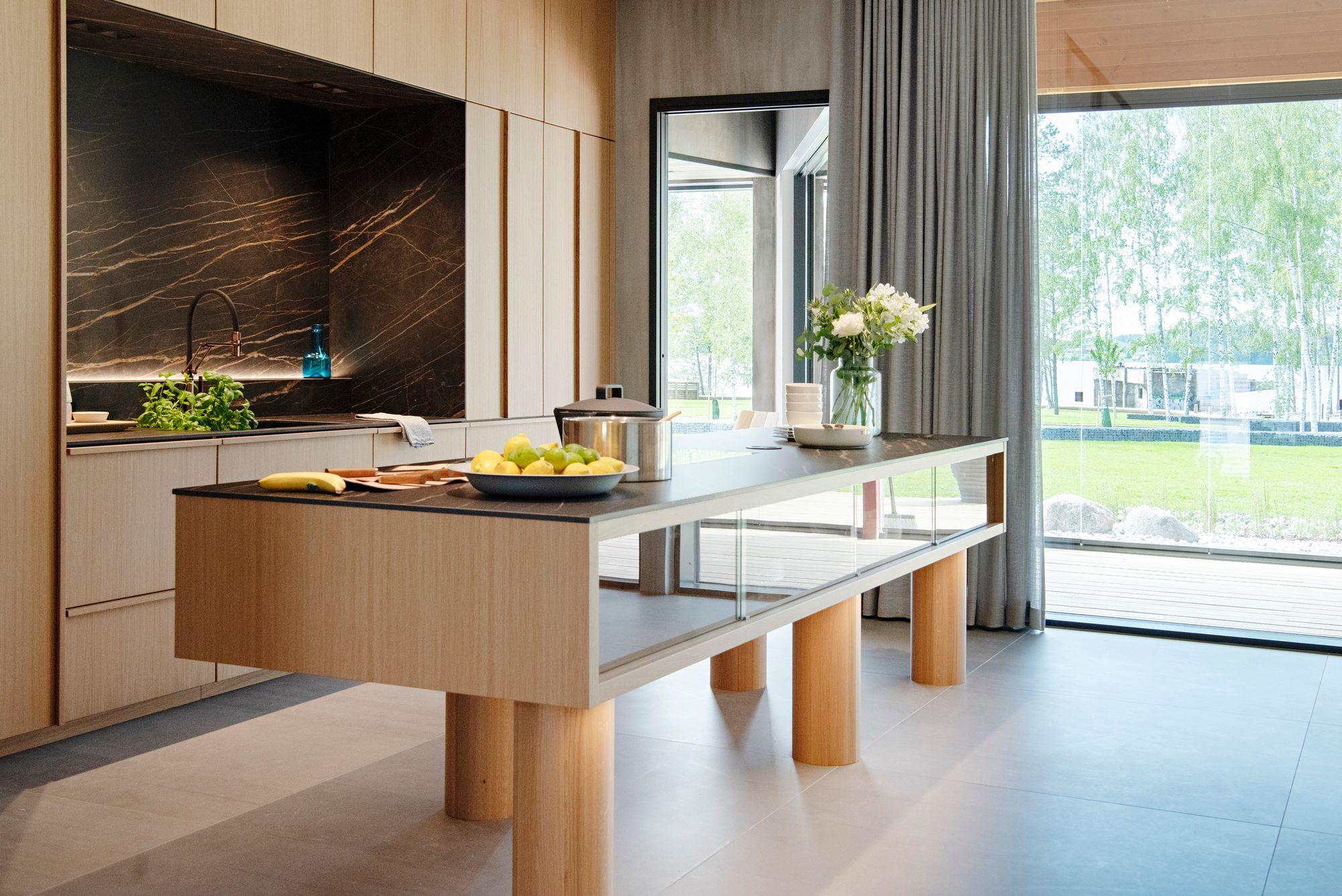 Keittiön tyylikäs saareke tuo lisää työ- ja säilytystilaa. Keittiön on suunnitellut Harri Koskinen. © Susa Junnola