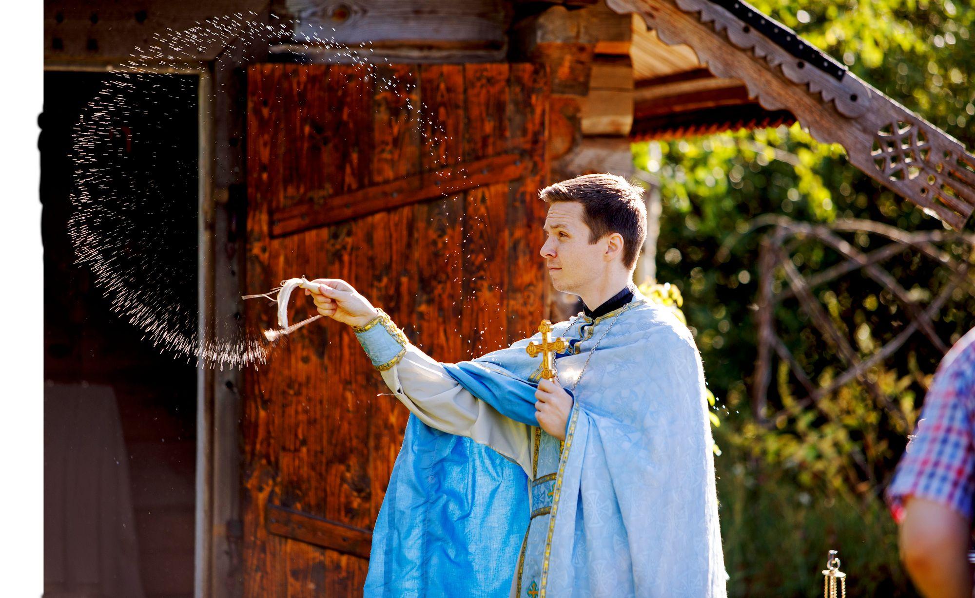 Pappi Kaarlo Saarento vihmoo pyhitettyä vettä tsasounan hirsisienille. © Hanna-Kaisa Hämäläinen