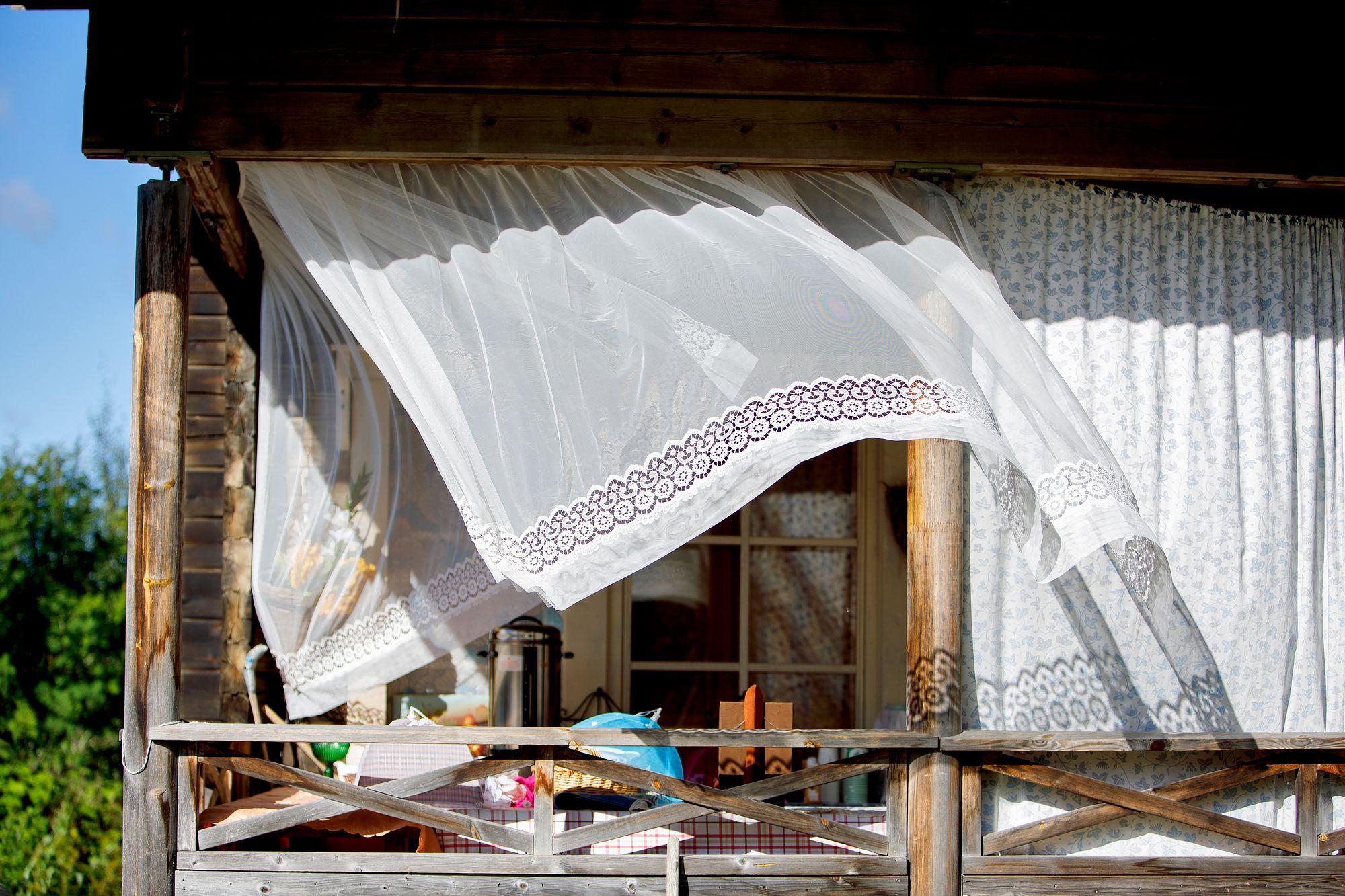 Talon terassilla praasniekkavieraat virkistäytyvät pöydän antimien äärellä ja vaihtavat kuulumisia. © Hanna-Kaisa Hämäläinen
