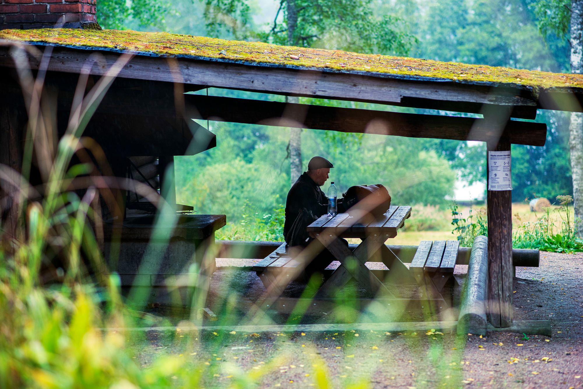 Keittokatoksen suojissa kelpasi lukea ja kuunnella sateen ropinaa. Taivasalla vietetyn yön jälkeen katos tuntui paikalta, jossa voisi olla päiväkausia. © Sampo Korhonen
