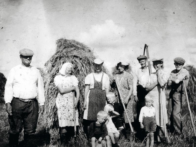 Heinäväki tauolla. Kun kaikki tehtiin vielä käsin, heinänteko oli koko perheen ja joskus kylänkin yhteinen työ. © Suur-Uskin kotialbumi