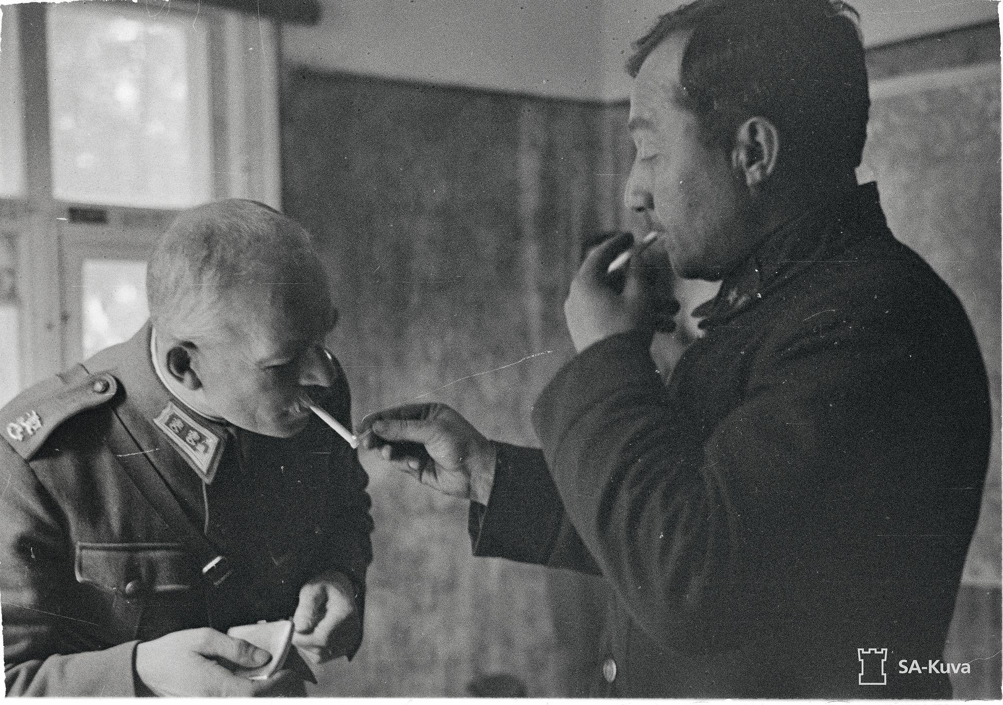 Kenraalimajuri Vladimir Kirpitšnikov sytyttää kohteliaasti kuulusteluhuoneessa kenraaliluutnantti Karl Lennart Oeschin savukkeen. © SA-Kuva