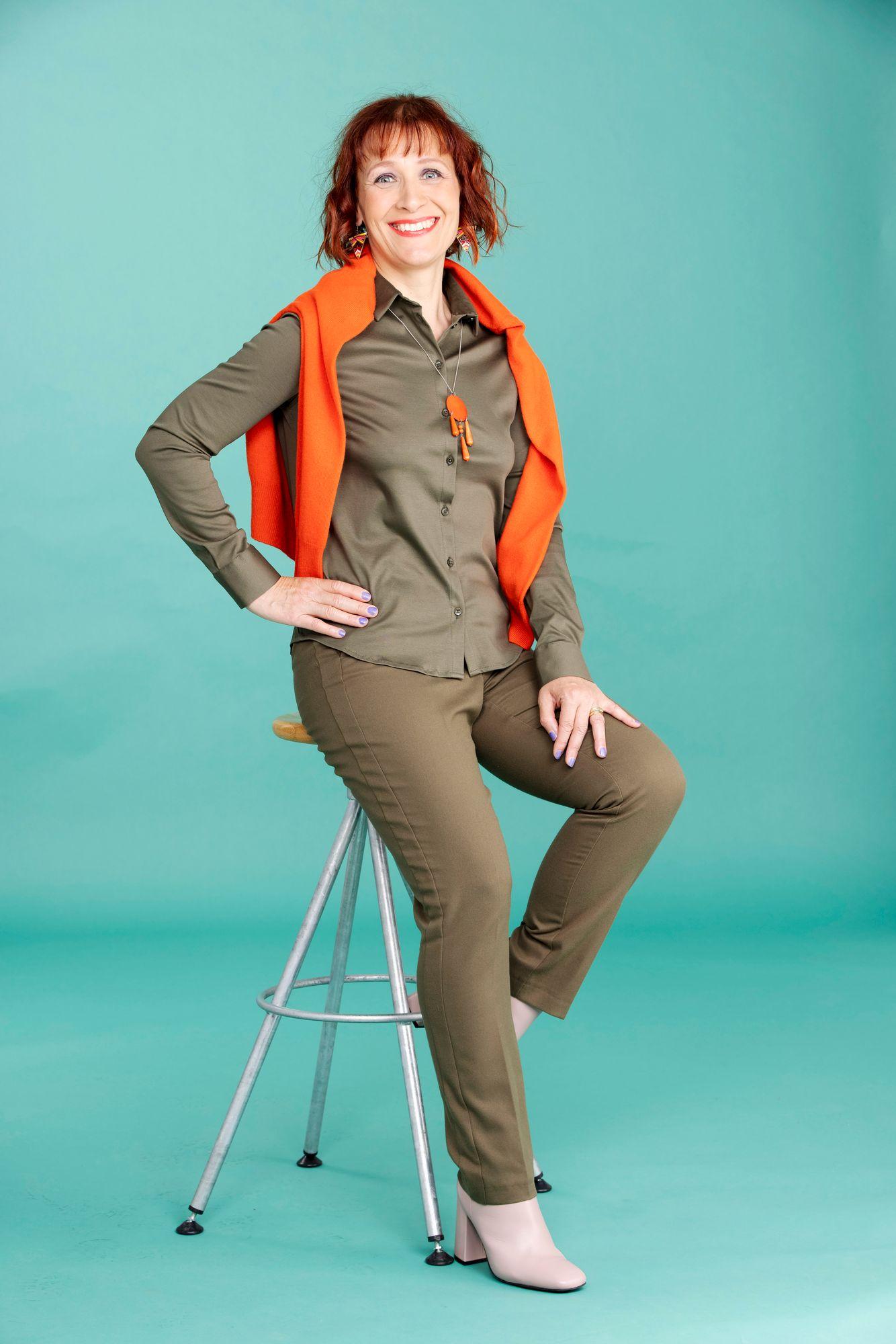 Oliivinvihreä paita ja housut näyttävät uniformulta. Oranssin värinen neuletakki ja korut tuovat asuun piristystä. Paita 109 € ja housut 109 €, molemmat Mos Mosh. Kashmirneuletakki 119 €, Mark & Spencer. Kaulakoru 32 €, Aarikka. Bootsit 199 €, Bella Luna. © Tommi Tuomi