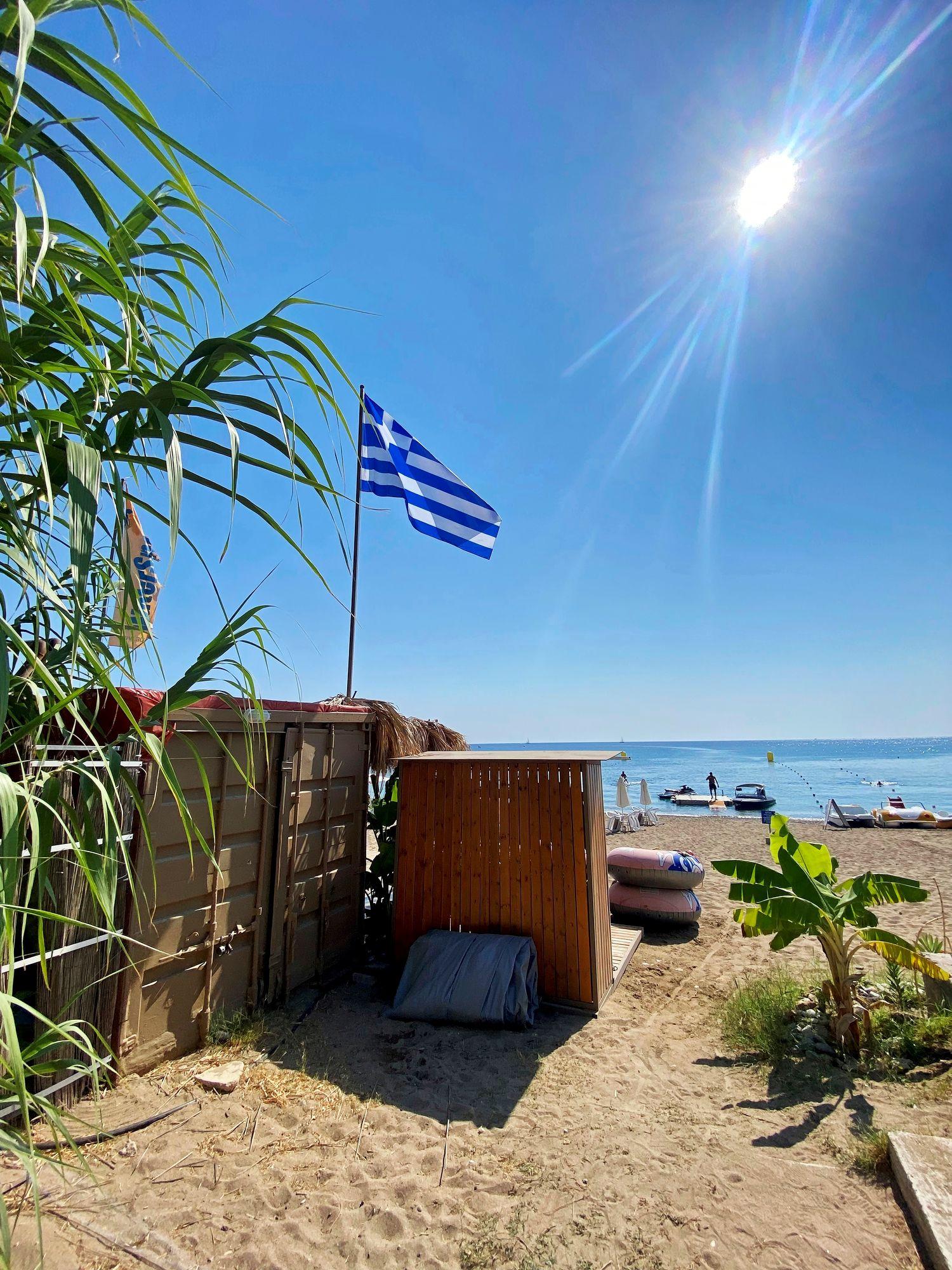 Saaren itärannikko tarjoaa hienoja pulahduspaikkoja, jotka vaihtelevat hiekasta kauniisiin kivirantoihin. Näin lippu liehuu Kallitheassa. © Liza Meriluoto
