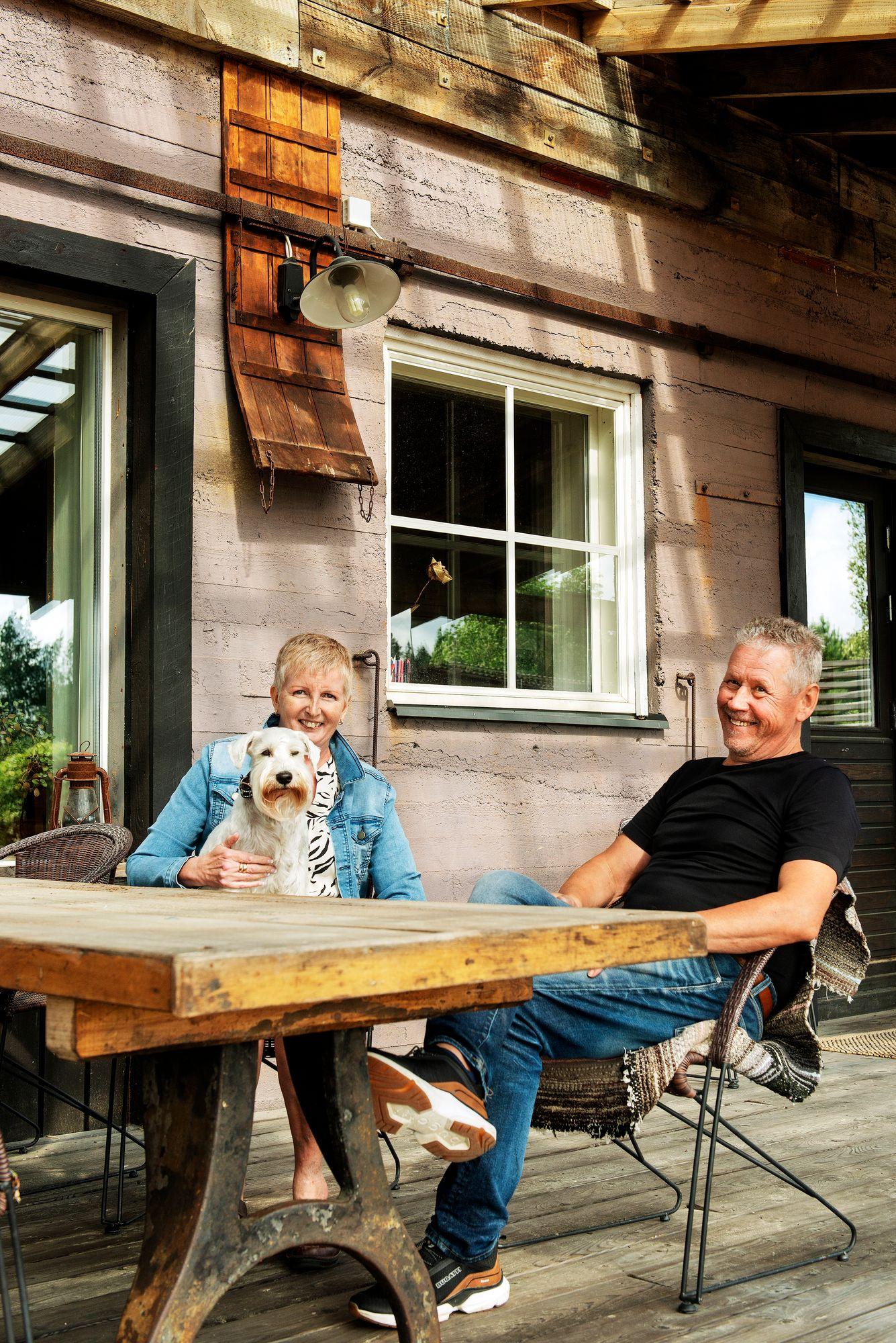 Terhi Kunelius ja Timo Peri nauttivat kesäpäivistä kotinsa terassilla. Ulkopöytä on vanhan mankelin taso. Timon ukki sai konepajan jalan istumaan runkoon just eikä melkein. © Linda Varoma
