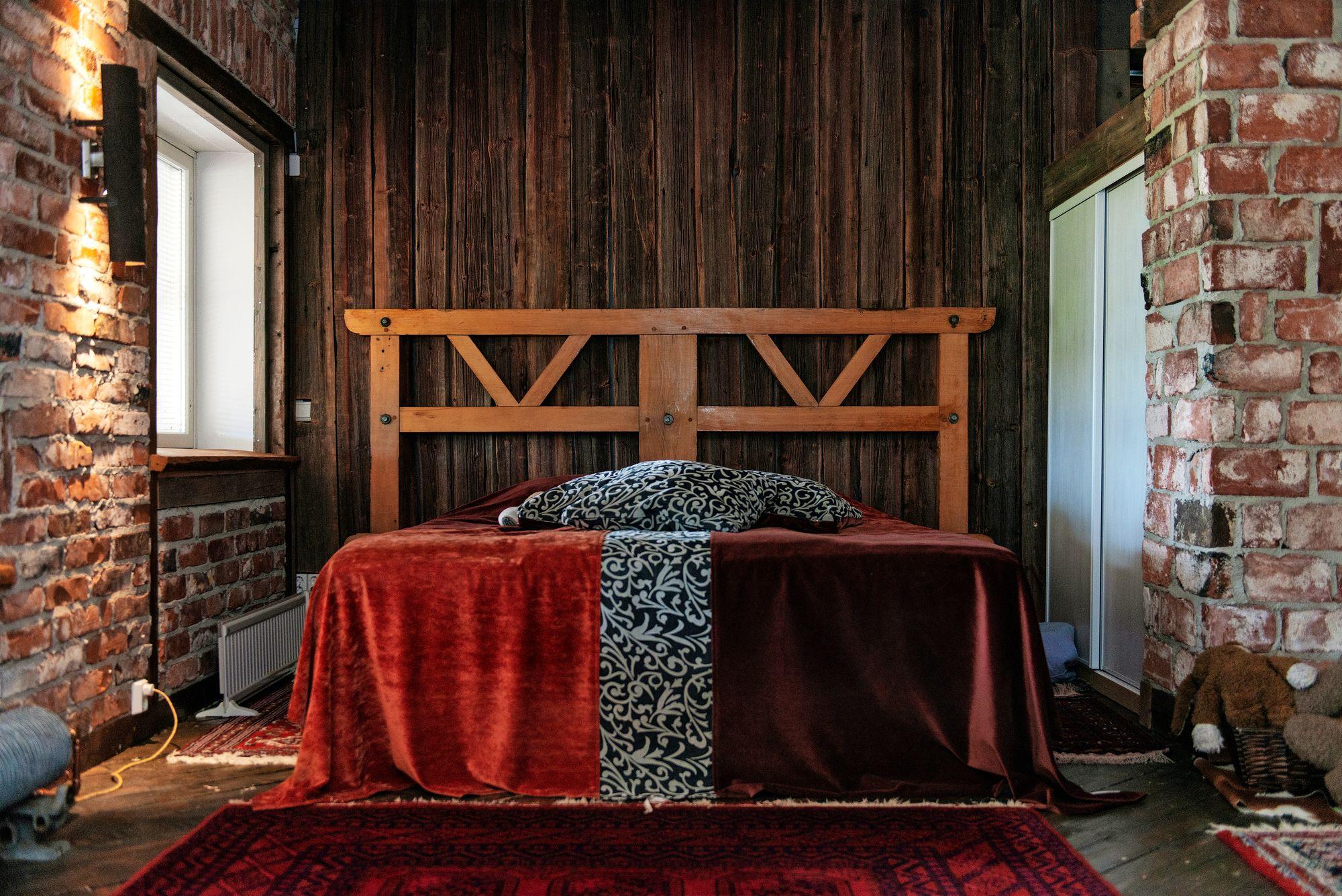 Sängyn pääty on osa mankelia. Seinä on vanhaa ladon lautaa. Samettipäällinen on ommeltu jämäpaloista. © Linda Varoma