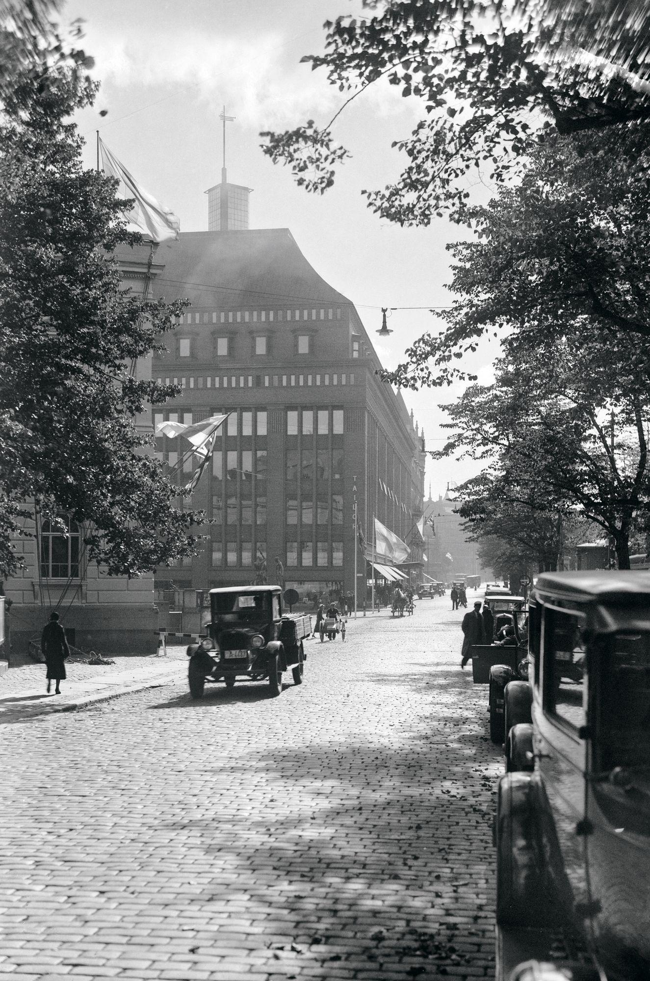 1930-luvulla pääkaupunkia halkovan Heikinkadun (nykyisen Mannerheimintien) keskikaista oli erotettu puilla – ja parkkipaikkoja riitti keskellä arkipäivääkin. © Helsingin kaupunginmuseo