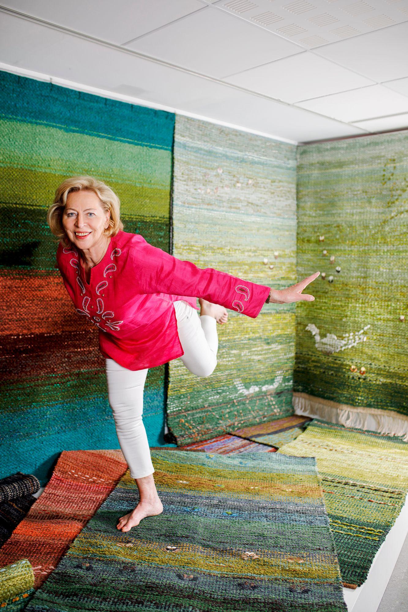 Virtaa täynnä oleva Eija Rasinmäki tekee tasapainoharjoituksia hänen suunnittelemassaan mattojen metsässä. © Hanna-Kaisa Hämäläinen