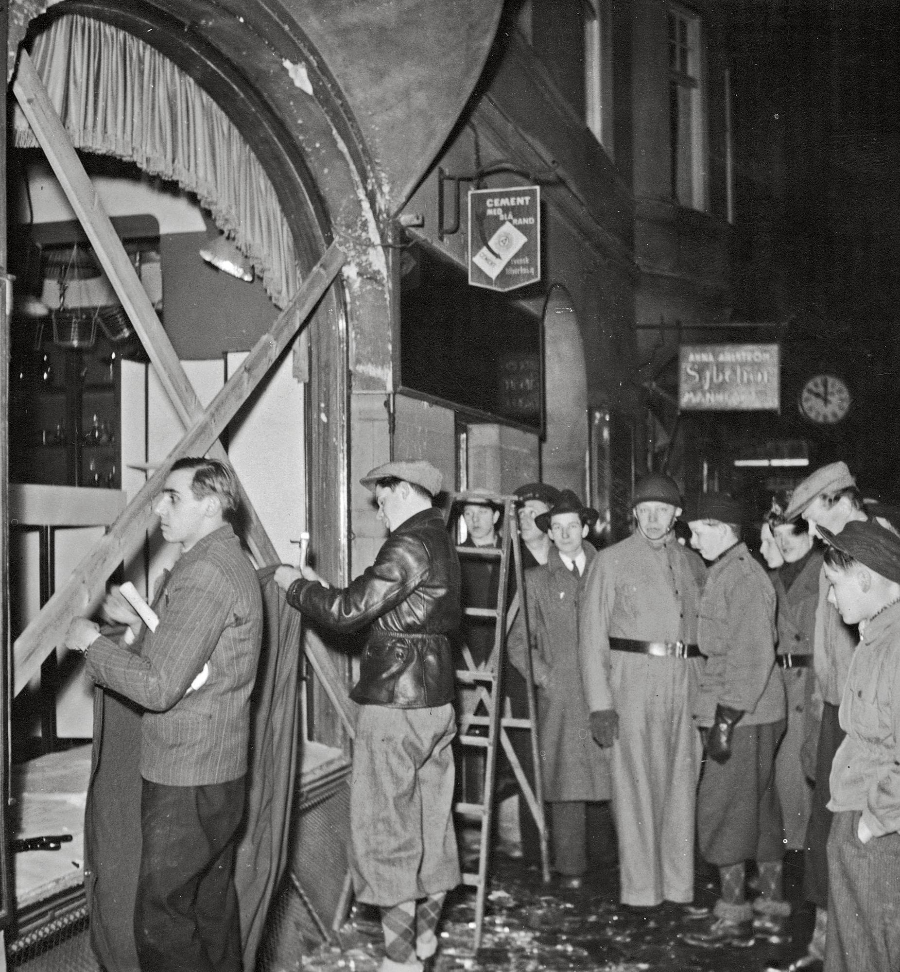 Tukholmalaismiehet kokoontuivat tutkimaan pommituksessa rikkoutuneen rautakaupan ikkunaa.