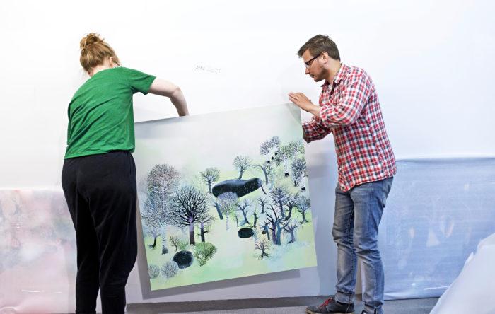 Kuvataiteilija-kuvittaja Aino Louhi ja Kasitonni purkavat Louhen maalauksia pakkauksista. Homma sujuu saksien puutteessa maaliraapalla ja hampailla.